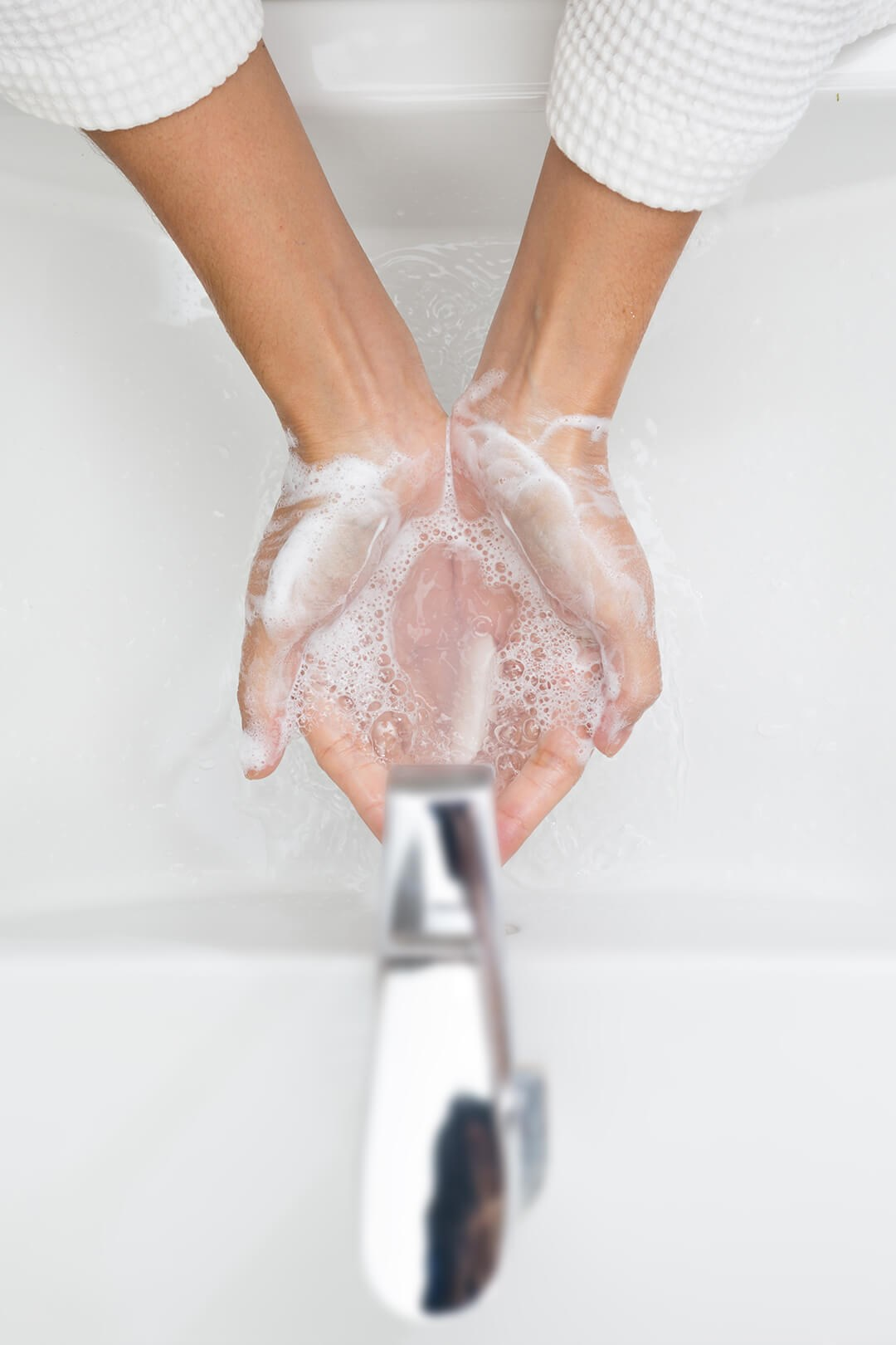 Soapy hands under tap