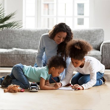Woman sitting in clean living room playing with her two children