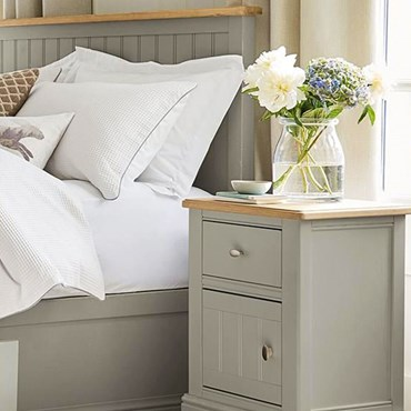 Bedside table in sage next to white bed sheets