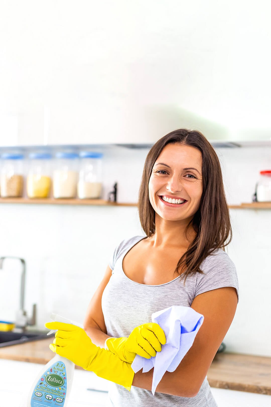 Woman smiling while wearing rubber cleaning gloves
